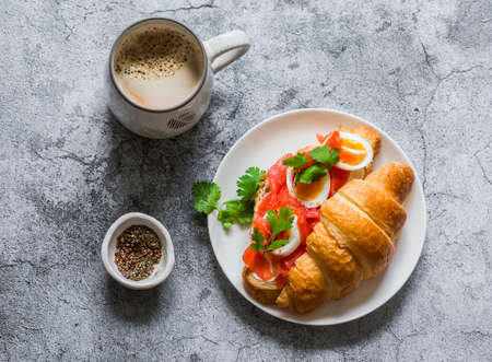 Delicious brunch - coffee with cream and croissant sandwich with cream cheese, salmon and boiled egg on a gray background, top view
