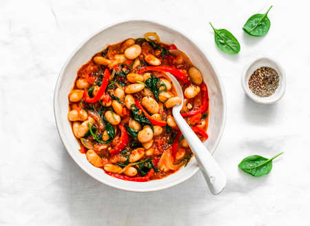 Greek style tomato sauce, spinach, paprika, beans stewed on a light background, top view