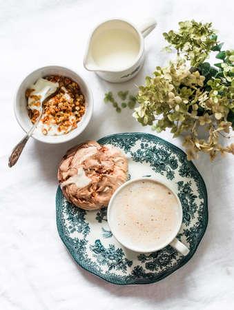 Cozy homemade breakfast - greek yogurt with granola, chocolate meringue, cappuccino on a light background, top view