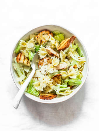 Caesar pasta salad in a bowl on a light background, top view. Delicious lunch, snack 版權商用圖片