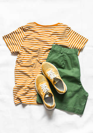 Women's cotton bermuda shorts, yellow t-shirt, white leather sneakers on a light background, top view. Fashion concept