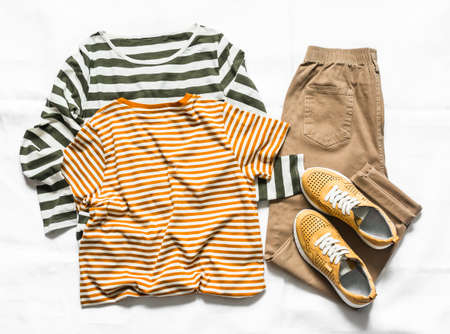 Women's clothing set - a pair of long and short sleeve t-shirts, suede sneakers and jogger pants on a light background, top view 版權商用圖片