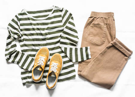 Women's slouchy pants, a long sleeve striped cotton t-shirt and suede sneakers on a light background. top view. Comfortable clothing for every day