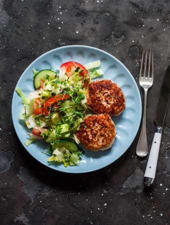 Chicken burgers and fresh iceberg, tomatoes, cucumber salad on a dark background, top view