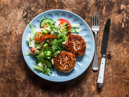 Turkey burgers and fresh iceberg, tomatoes, cucumber salad on a wooden background, top view. Balanced lunch