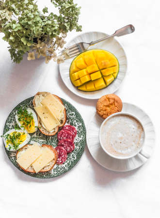 Delicious brunch - cappuccino, fresh mango, boiled egg with micro greens, salami, cheese sandwiches on a light background, top view