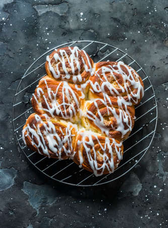 Lemon sugar buns with icing on a dark background, top view. Delicious homemade dessert
