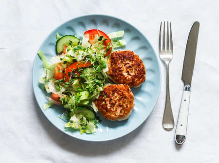 Chicken burgers and fresh iceberg, tomatoes, cucumber salad on a light background, top view
