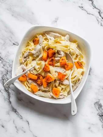 Fettuccine with chicken and baked pumpkin in cream sauce on a light background, top view. Delicious mediterranean style lunch