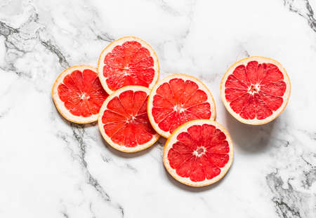 Slice of fresh ripe grapefruit on a marble light background, top view