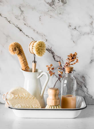 Kitchen interior. Tray with tools for washing dishes - brushes, natural dishwashing detergent, loofah sponge on a light background Archivio Fotografico
