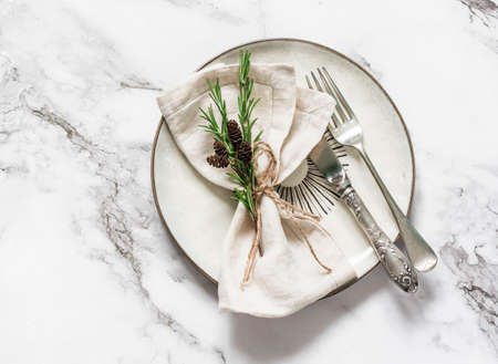The idea of decorating a serving napkin with a sprig of rosemary. Plate, napkin, cutlery on a light background, top view
