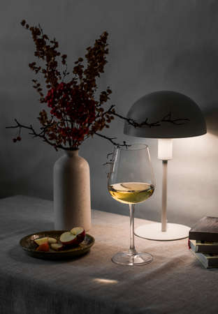 Cozy evening home still life - glass of wine, lit lamp on the table. Scandinavian style interior Archivio Fotografico