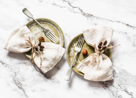 Idea of serving is vintage ceramic plates and linen napkins decorated with cones and nuts on a light marble background, top view