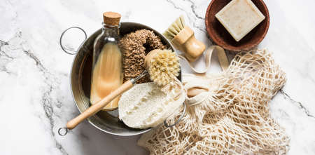 Banner concept accessories for kitchen cleaning - natural bristle brushes, loofah sponges, natural soap and enamel basin on a marble light background, top view