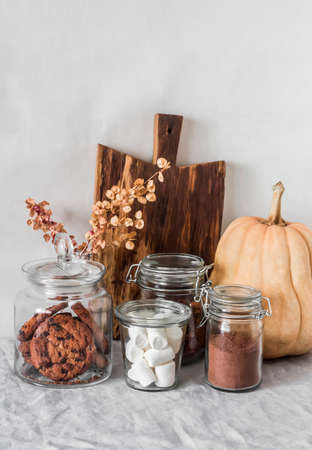 Ingredients for making hot chocolate - cocoa, marshmallows, oatmeal cookies with chocolate drops on the table in the room Archivio Fotografico