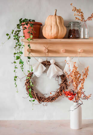 Cozy interior of the hallway. Wooden hanger with flower, pumpkin, grape wreath and homemade paper ghost garland
