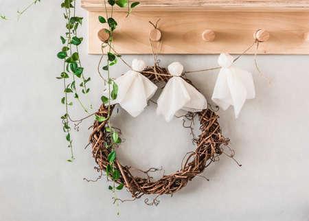 Halloween children's crafts - paper ghosts from napkins garland on a wooden hanger in the hallway. Creativity craft concept Archivio Fotografico