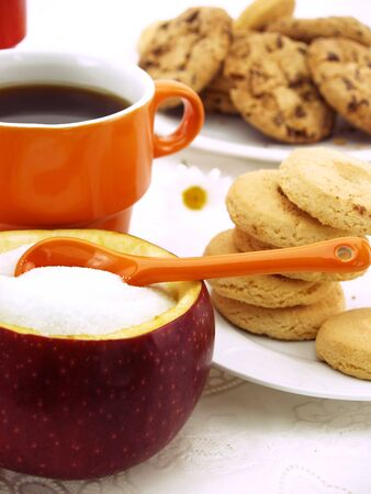 fructose: Sugar bowl made of red apple with fructose inside, set on table with coffee and cookies