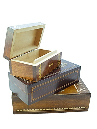 Wooden jewellery boxesThree wooden jewellery boxes piled one on top on an other, the top one is opened isolated on white photo