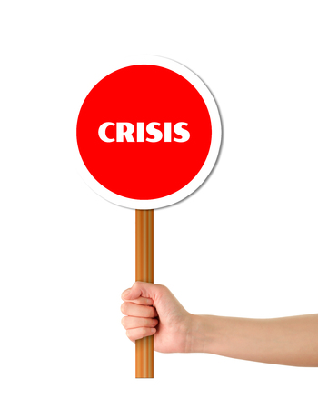 unsustainable: Hand holding crisis red sign
