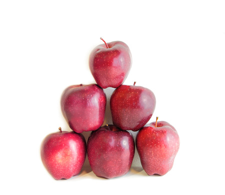 A pyramid of red organic apples isolated on white photo