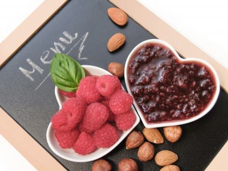 Raspberries and raspberry jam in heart white bowls Stock Photo