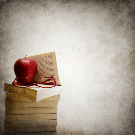 Grunge background with stack of books, apple and eyeglasses photo