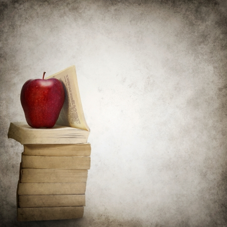 Grunge background with stack of books and red apple photo