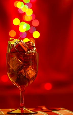 Festive red background with glass, present boxes and bokeh photo