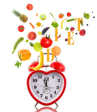 Clock in shape of heart with fruits and vegetables. photo