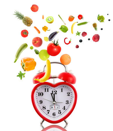 Clock in shape of heart with fruits and vegetables. Stock Photo