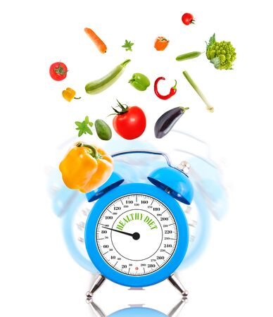 Diet concept with clock, scale dial and vegetables. photo