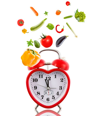 Clock in shape of heart with vegetables. photo