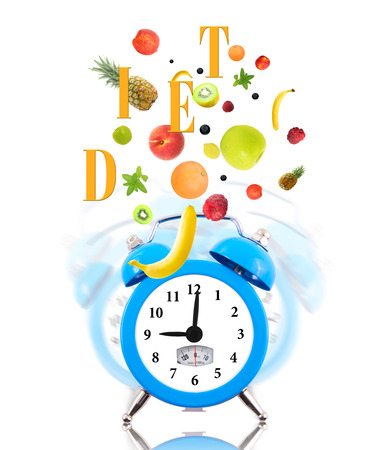 Diet concept with clock, scale dial and fresh fruits photo