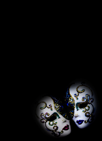 Two beautiful masks emerge from darkness