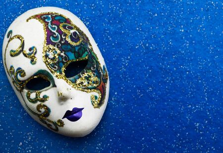 Beautiful mask on blue background with glitter photo