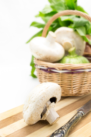 Mushrooms with wicker basket,greens and vegetables isolated photo