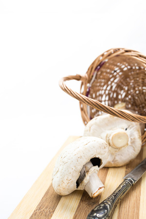 Mushrooms in wicker basket, cutting board and knife with copy-space photo