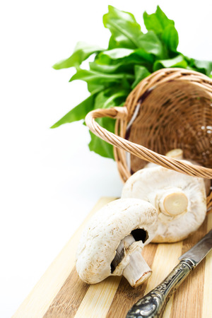 Mushrooms in wicker basket,greens and knife with copy-space photo