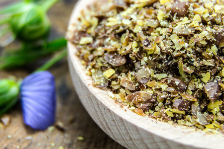 Brown flax seed meal with blue flower petals closeup  photo