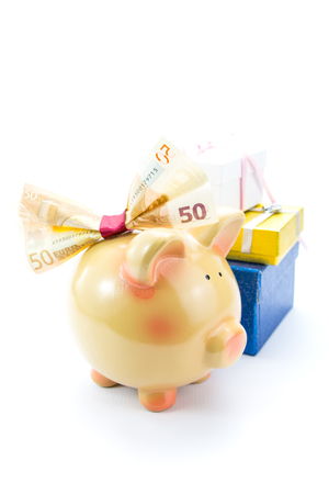 Piggy bank with a banknote bow and gift boxes photo