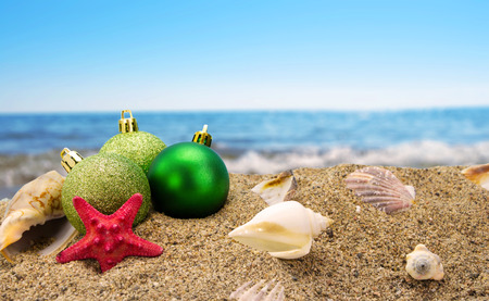 Kerst ballen en schelpen op zand met zomer zee achtergrond Stockfoto
