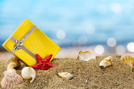 Gold gift box on sand with summer sea background  photo
