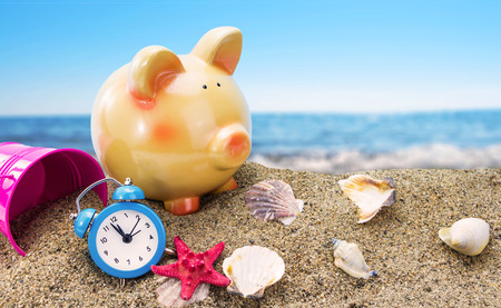 Piggy bank on sand with summer sea background  photo