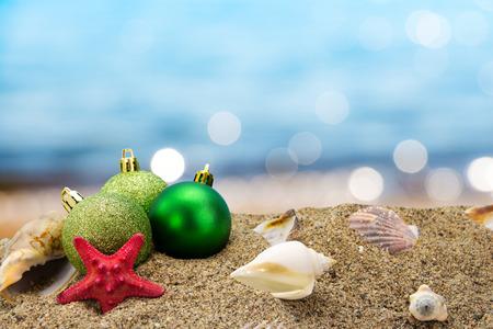 tropical christmas: Christmas balls and shells on sand with summer sea background  Stock Photo