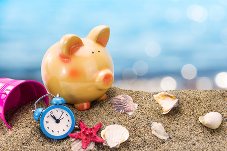 Piggy bank on sand with summer sea background
