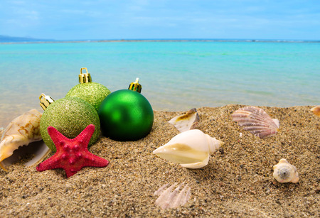 merry time: Christmas balls and shells on sand with summer sea background  Stock Photo