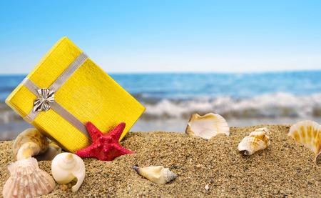 Caja de regalo de oro en la arena con el mar de fondo de verano Foto de archivo