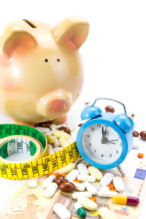 Piggy bank with pile of pills, banknotes clock and measure tape  photo